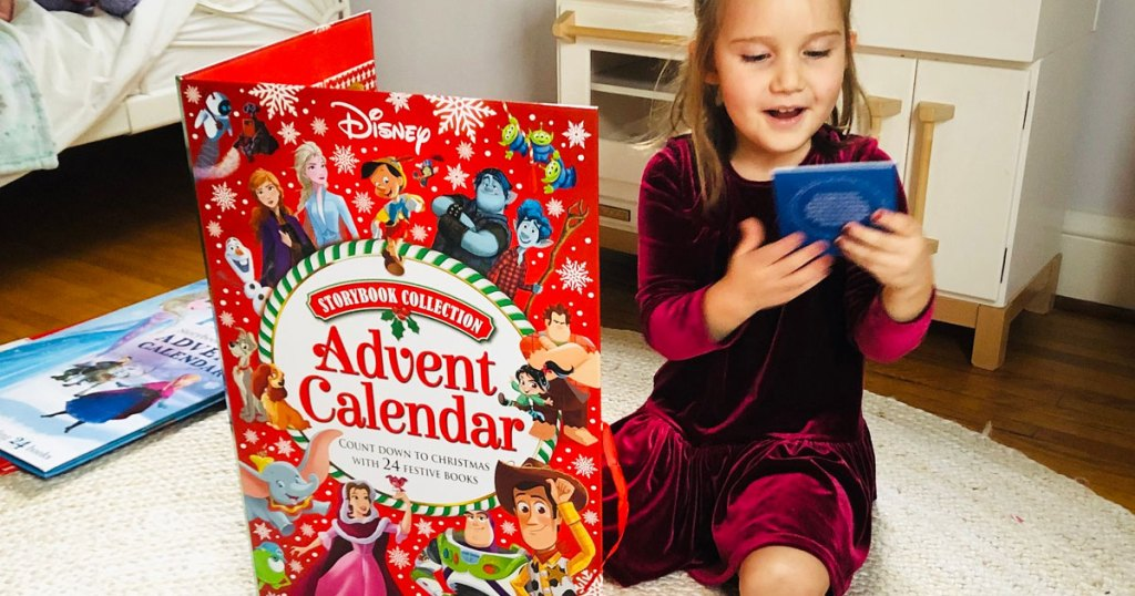 girl in a red velvet dress on floor next to big red disney storybook advent calendar