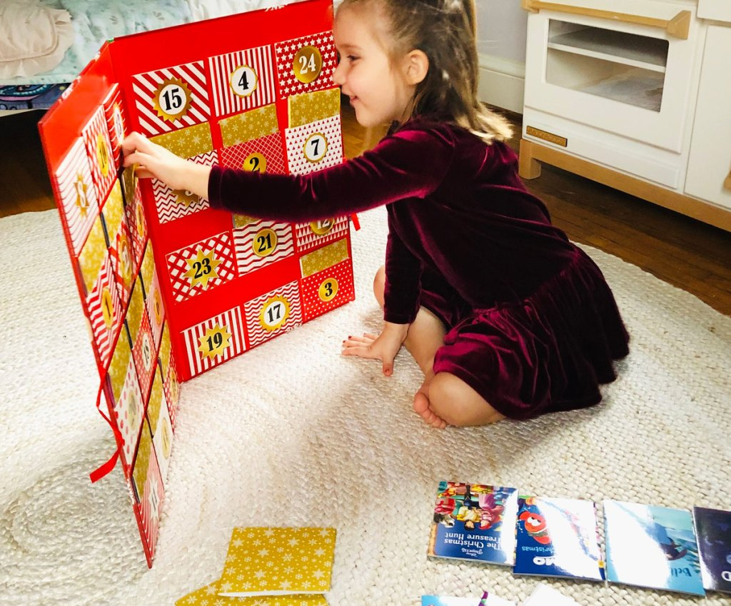 girl in red velvet dress pulling a book from the disney storybook advent calendar