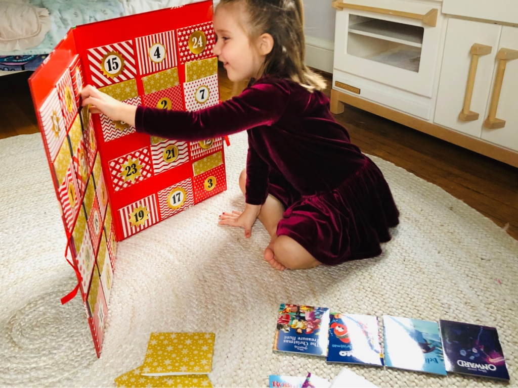 girl on bedroom floor with large storybook advent calendar