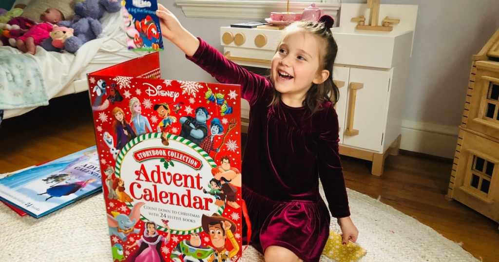 girl on bedroom floor holding book from large Disney advent calendar