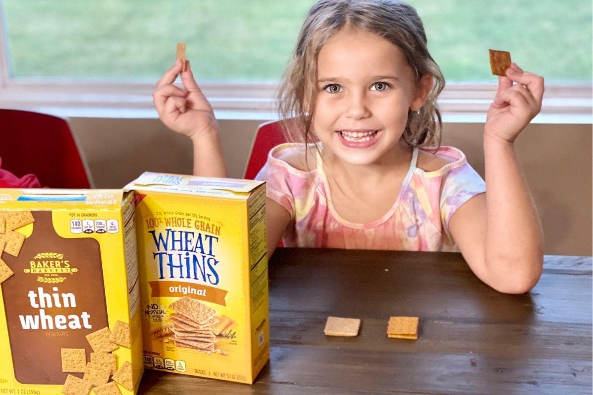 Seorang gadis kecil di meja dengan biskuit di tangan