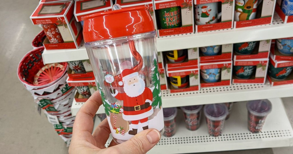 person holding up Santa print kids tumbler with red swirly straw inside in front of other christmas mugs on display at dollar tree