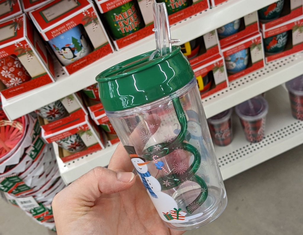 person holding up snowman printed kids tumbler with green swirly straw inside
