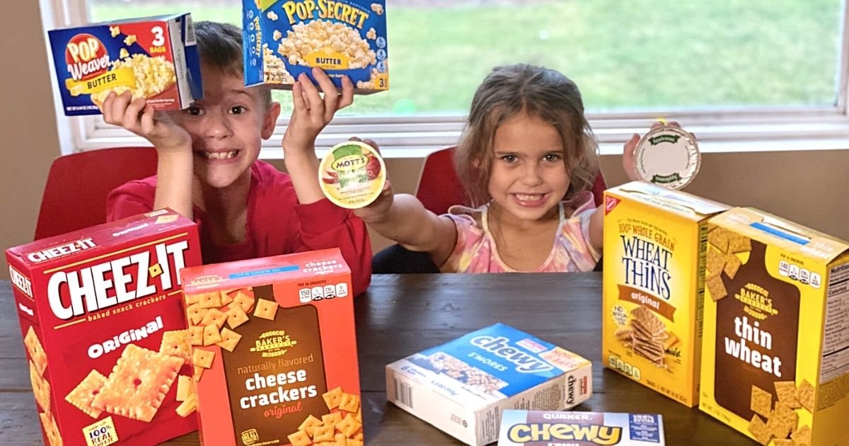 Two kids sitting at a table with various snacks