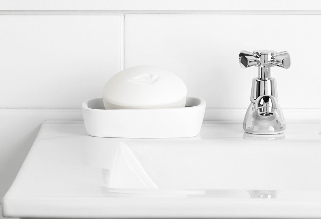 dove beauty bar in white soap dish on white bathroom sink
