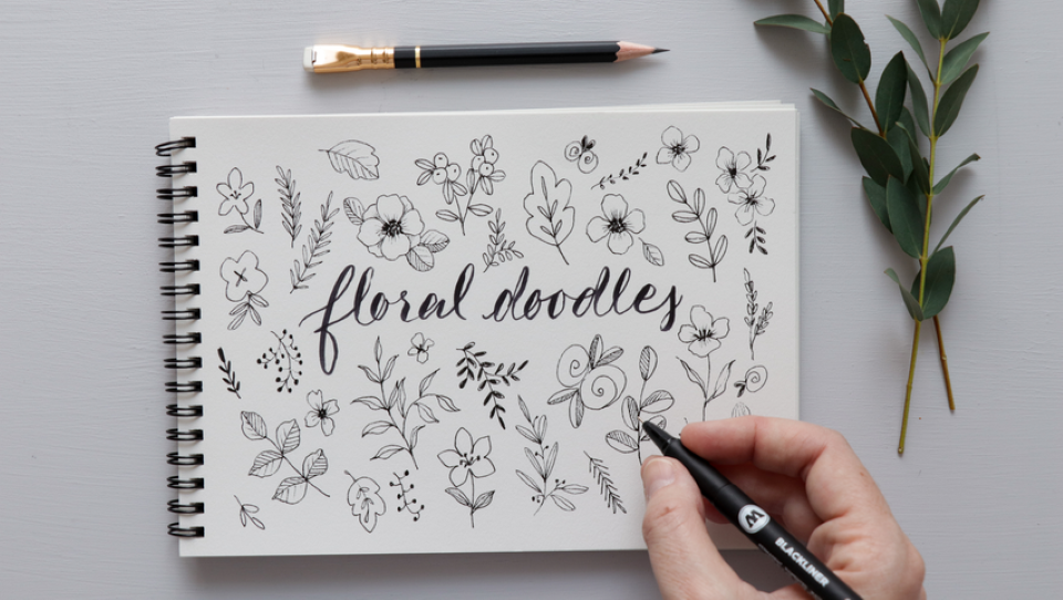 hand doodling flowers on a sketchpad