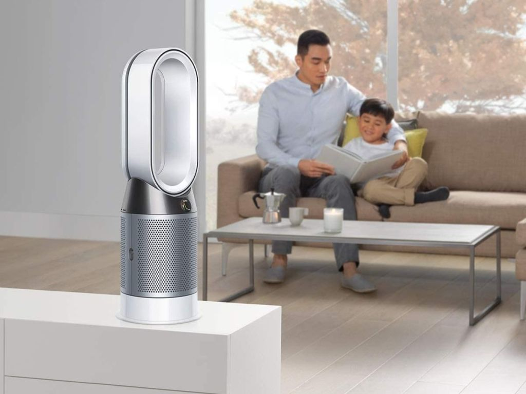 silver Dyson air purifier on white ledge with man and boy reading on couch in background