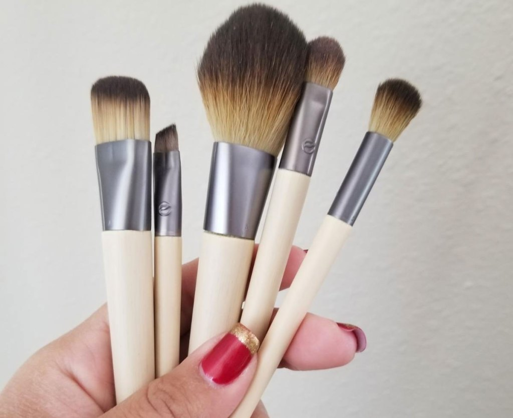 woman with red nails holding up a set of 5 makeup brushes