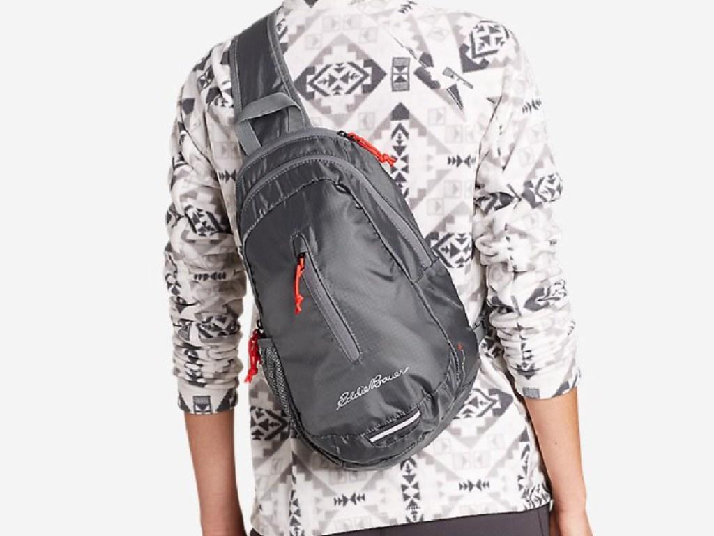 woman wearing a light grey eddie baur packable sling bag