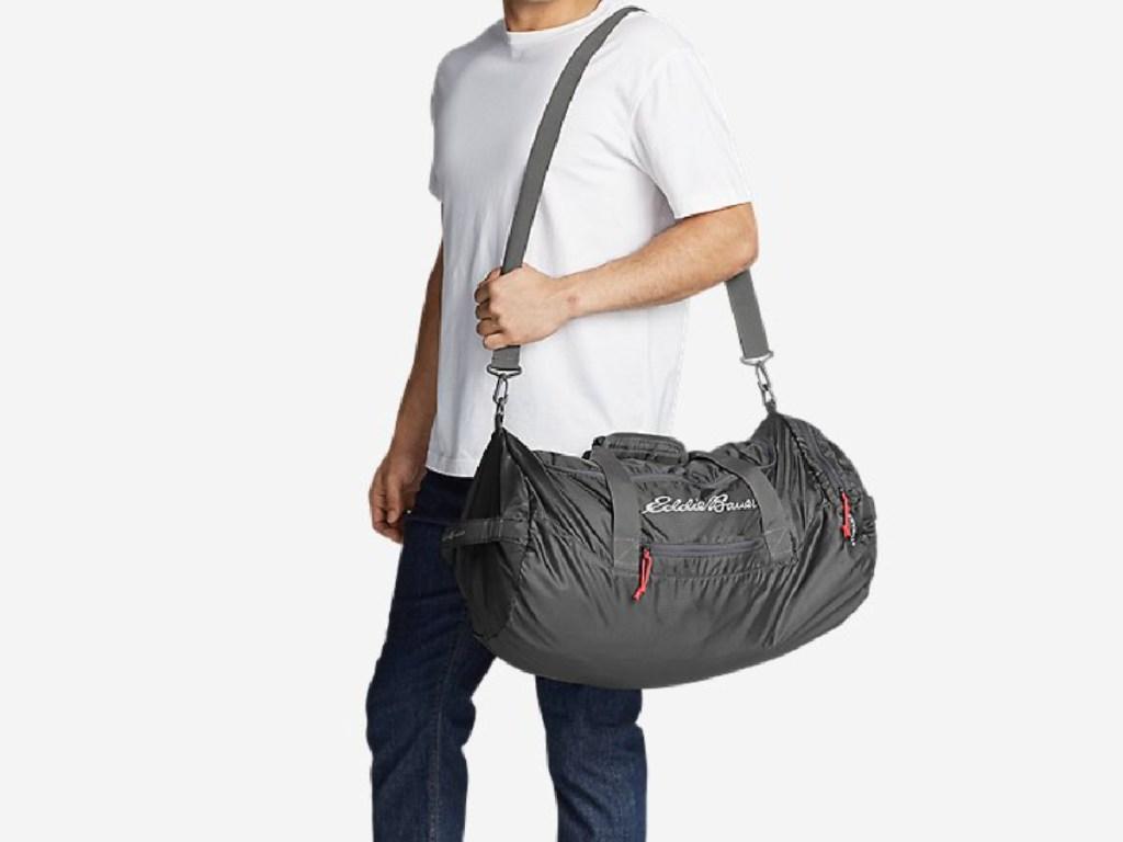 man carrying a grey eddie bauer packable duffel bag