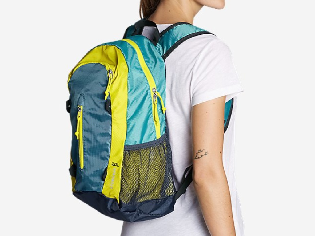 woman wearing a colorful packable eddie bauer backpack