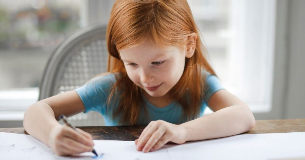 girl coloring on a worksheet