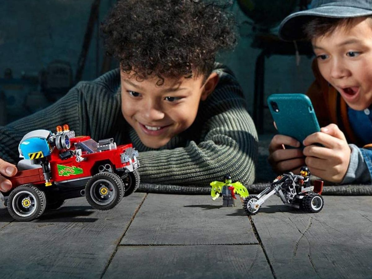 two boys playing with the El Fuego Stunt Show LEGO Set