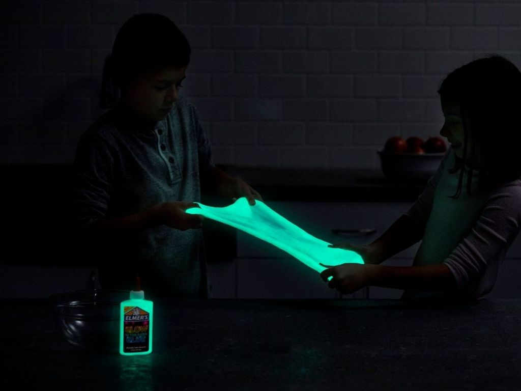 kids playing with glow in the dark slime with Elmer's glow in the dark glue bottle in front of them