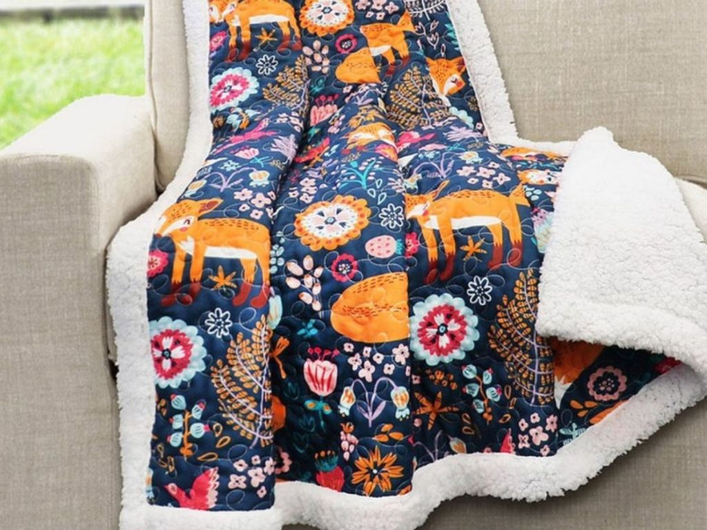 Essential Living Sherpa Lined Throw with Fix print draped over a chair