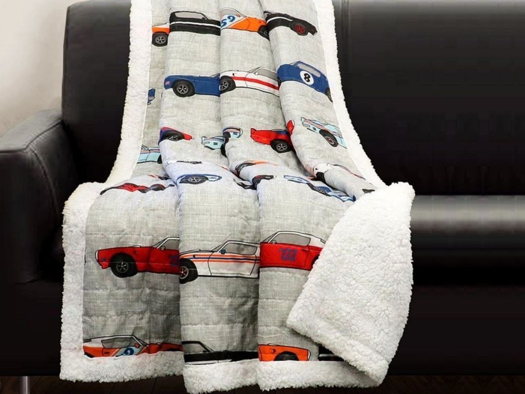 Sherpa Lined Quilt with Race Cars Print thrown on couch