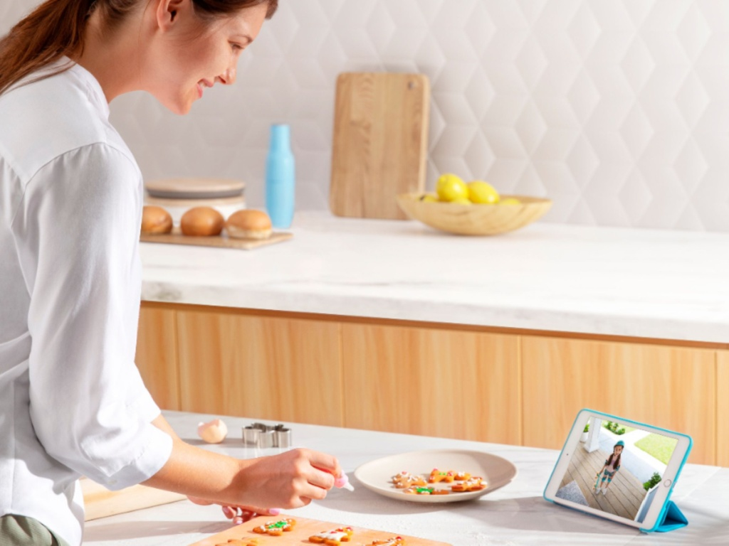 woman standing at a kitchen counter cooking while watching a security camera on a blue tablet