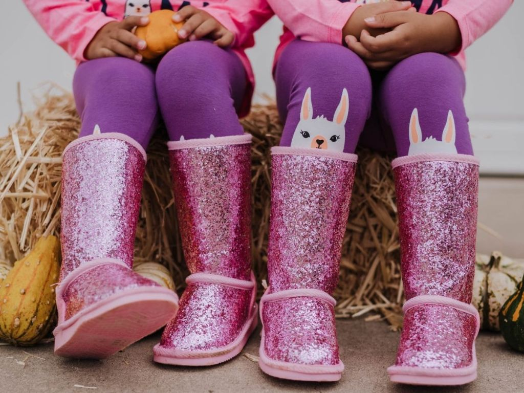 girls sitting on hay bale wearing pink sparkle boots