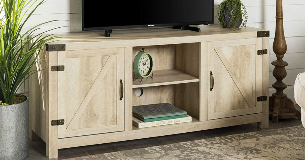 farmhouse tv stand with white oak finish and tv on top of it