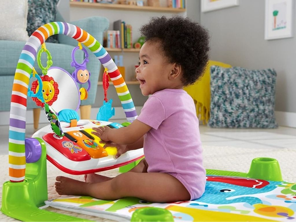 Fisher Price Kick and Play Piano with little girl sitting up playing with it