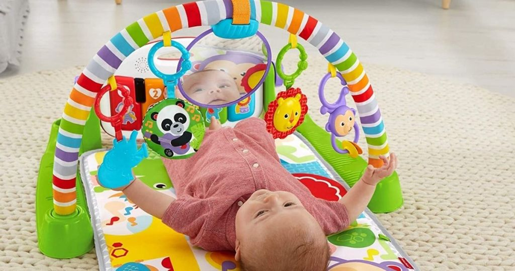 Baby laying on Fisher Price kick and play piano toy