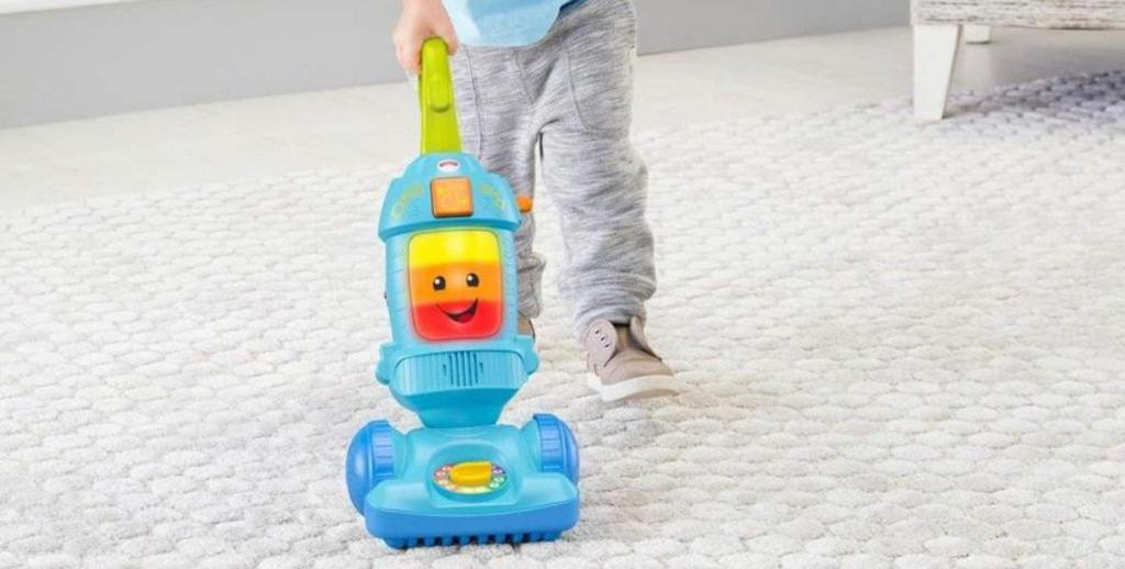 child pushing Fisher-Price Laugh & Learn Light-up Learning Vacuum on carpet