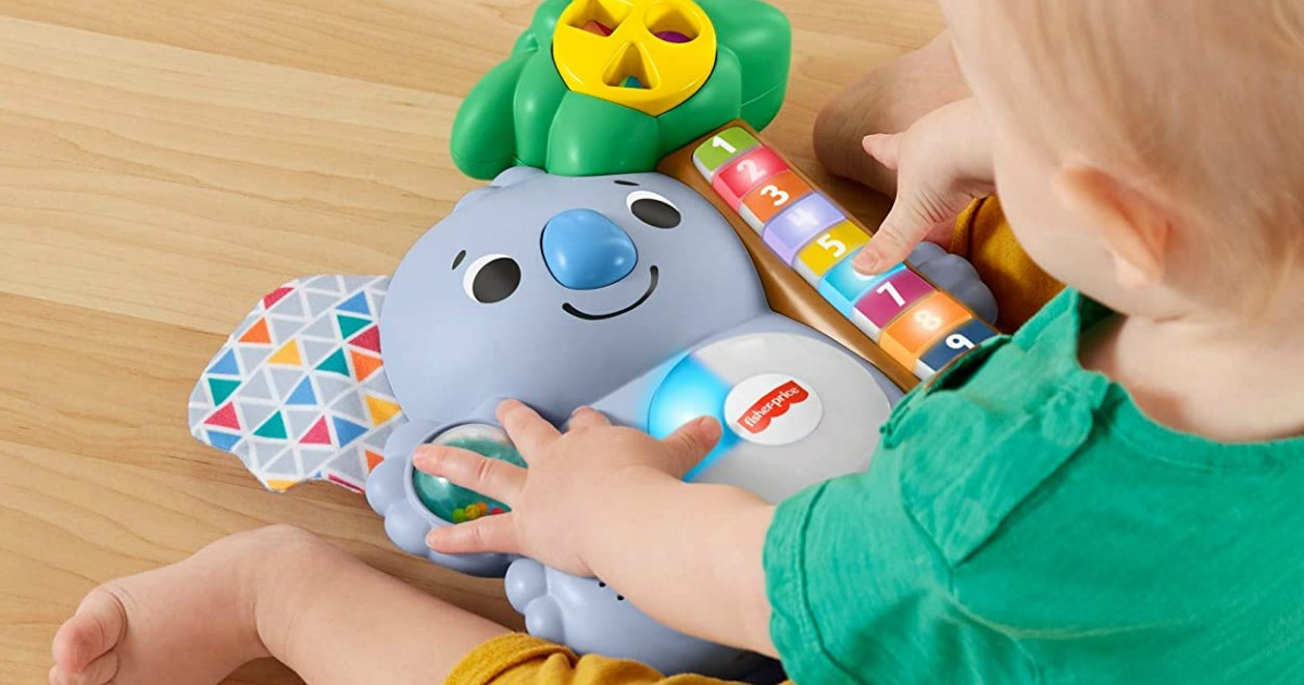 toddler playing with a Fisher-Price toy