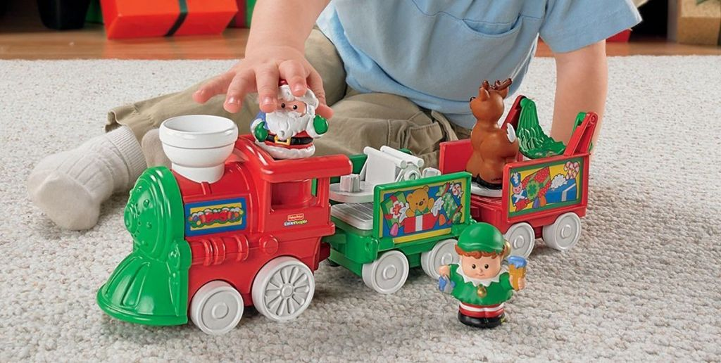kid playing with Fisher-Price Little People Musical Christmas Train