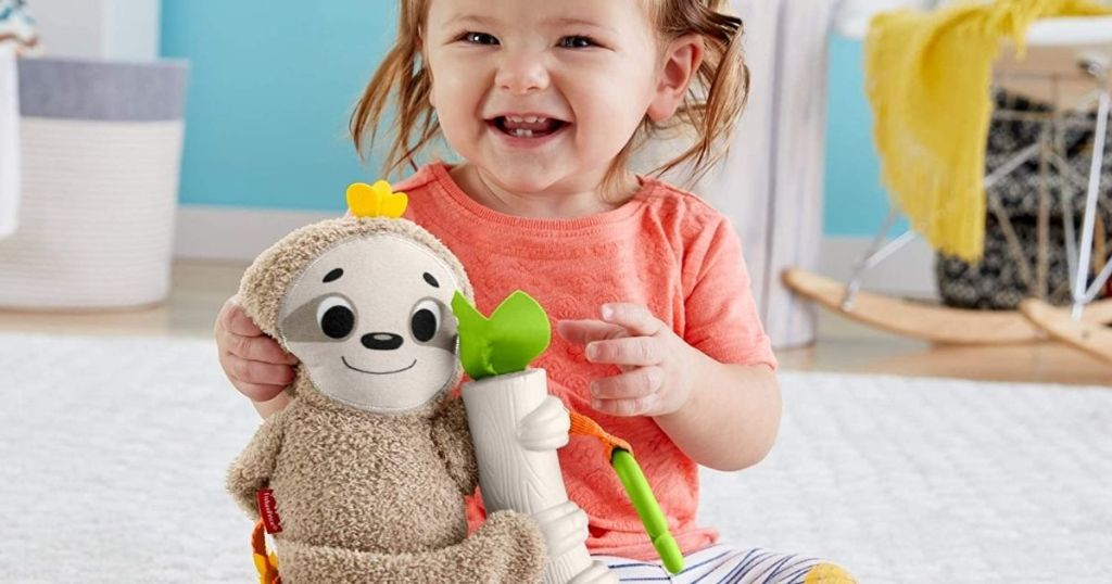 baby girl holding onto a toy sloth