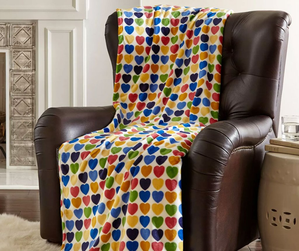 multi color heart print throw blanket draped on a leather chair