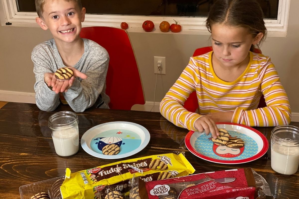 Two kids eating cookies at a table