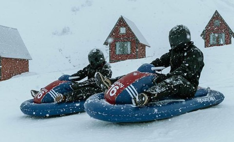 two people on inflatable snowmobiles