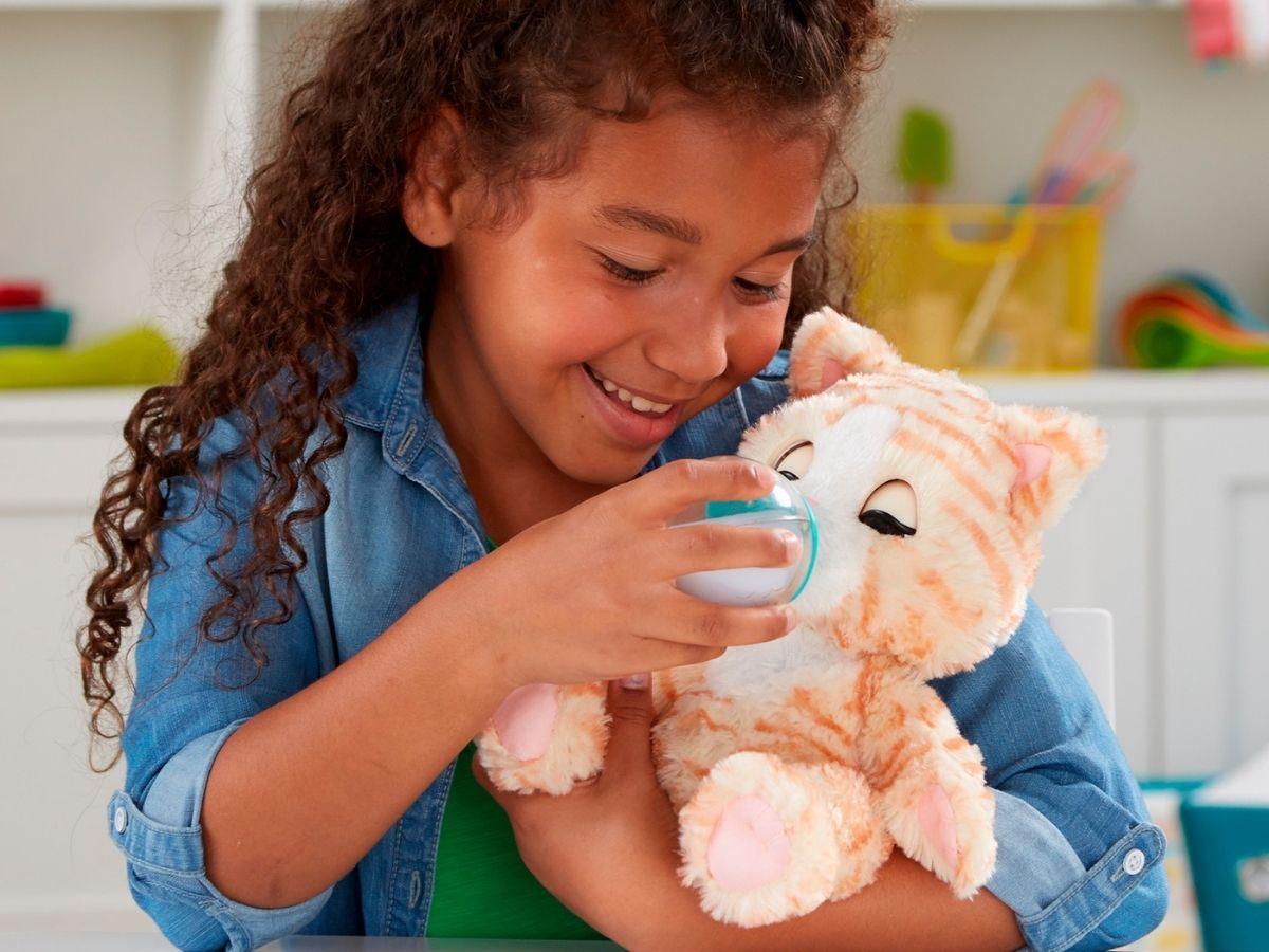girl feeding toy kitten a bottle