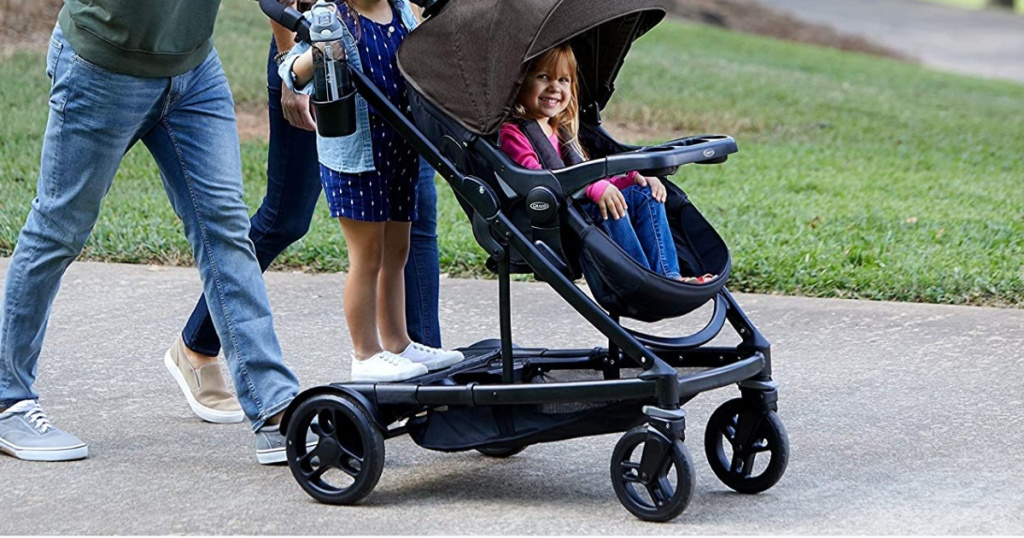family walking with one child standing and one sitting in double stroller