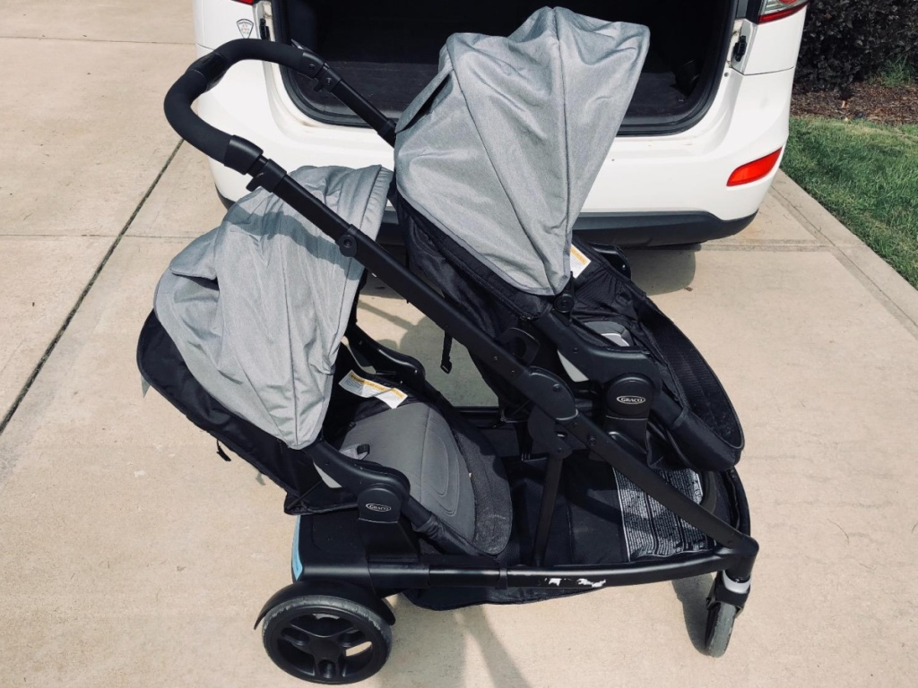 black and gray double stroller in front of white van