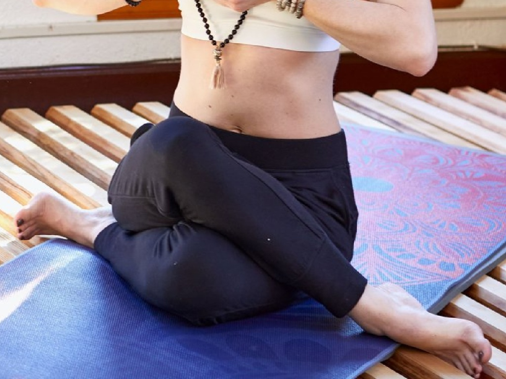 woman sitting on yoga mat in white top and black joggers