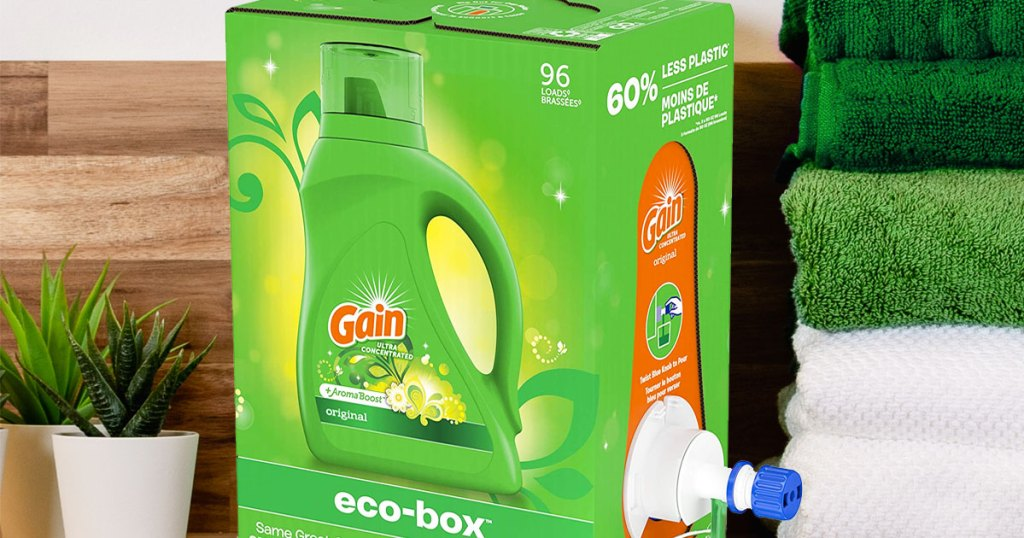 green box of gain laundry detergent near stack of folded towels and potted plants