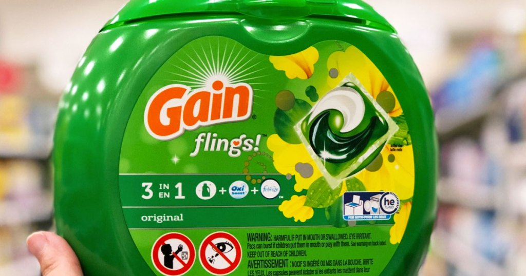 person holding up green container of gain flings