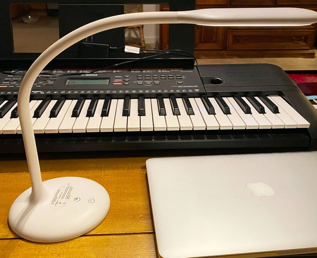 white desk lamp shining over a piano keyboard and macbook on wood table