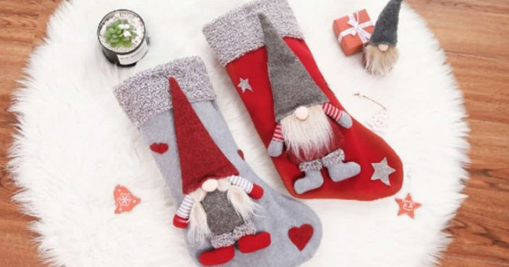 two red and grey gnome stockings on white rug