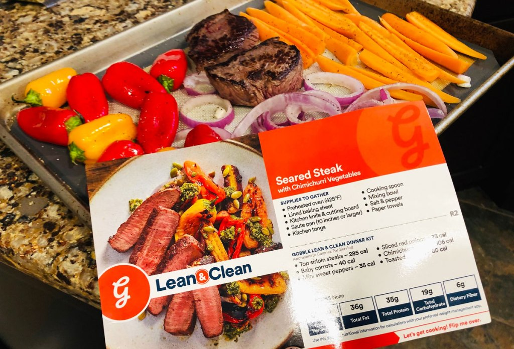 woman holding up Gobble recipe card for seared steak meal with ingredients on baking sheet in background