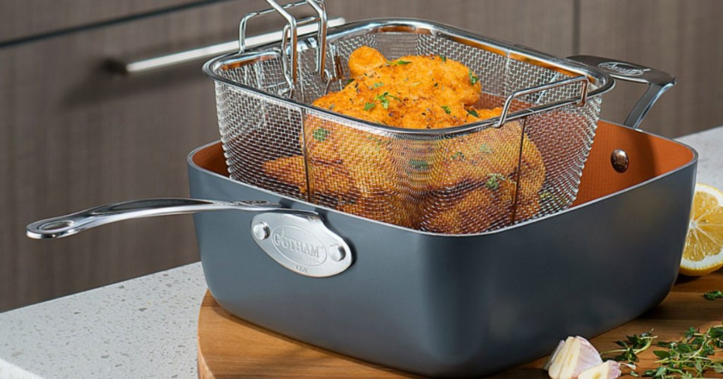 gotham steel deep square fry pan on cutting board with frying basket in it holding fried foods