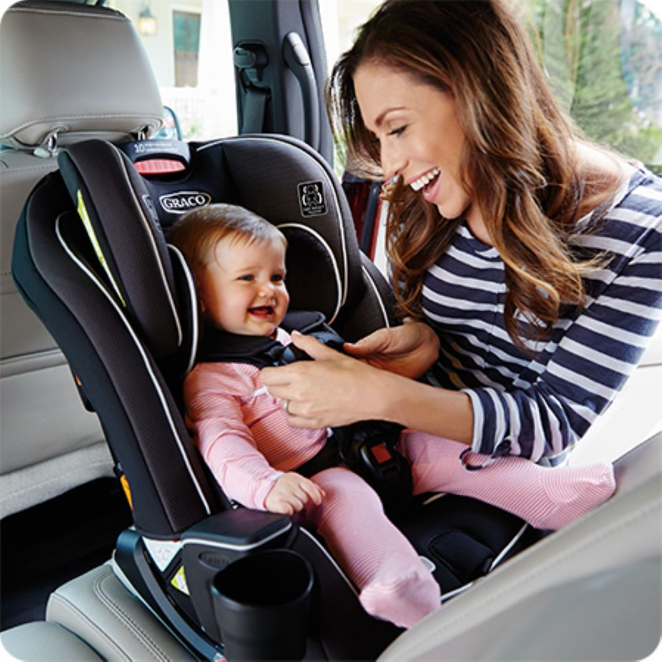 woman buckling a baby into a carseat