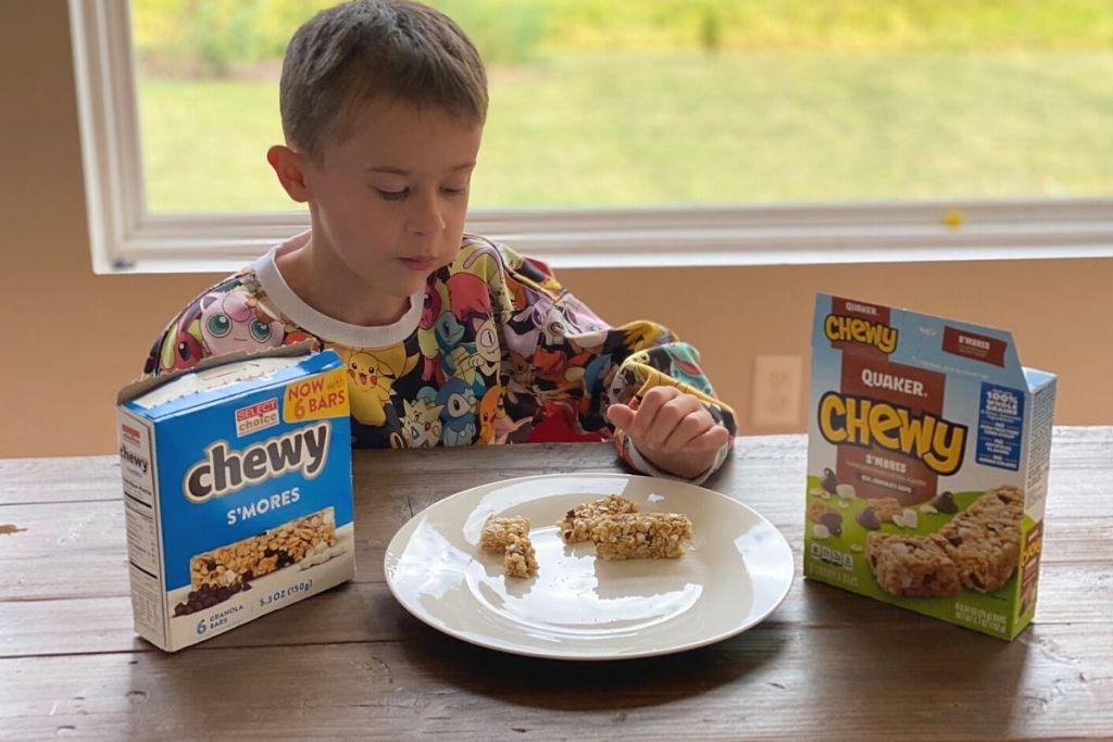 Seorang anak laki-laki sedang makan granola batangan di piring di sebelah kotak