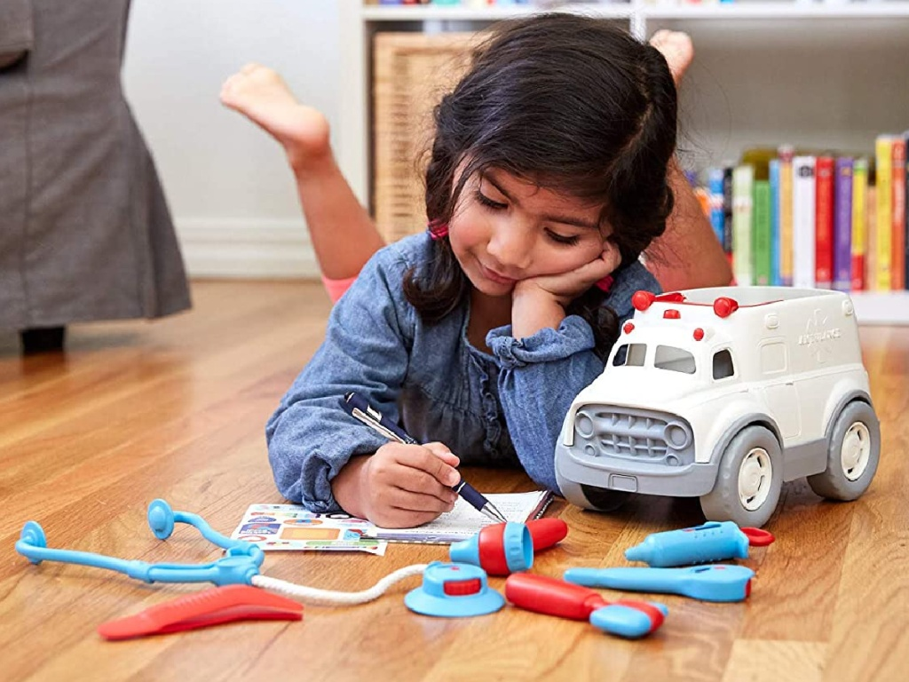 girl playing with toy ambulance and doctor accessories on hardwood floor