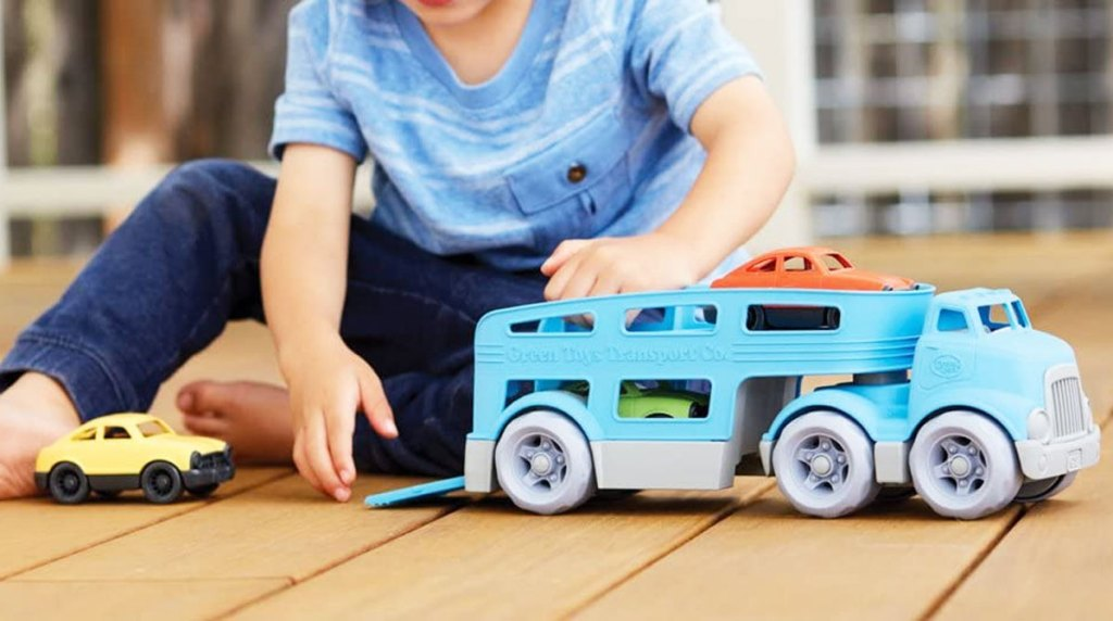 boy playing with a blue car carrier truck with three cars
