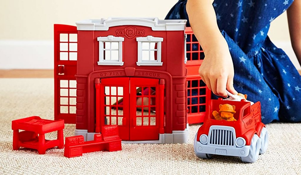 girl playing with a red fire station playset