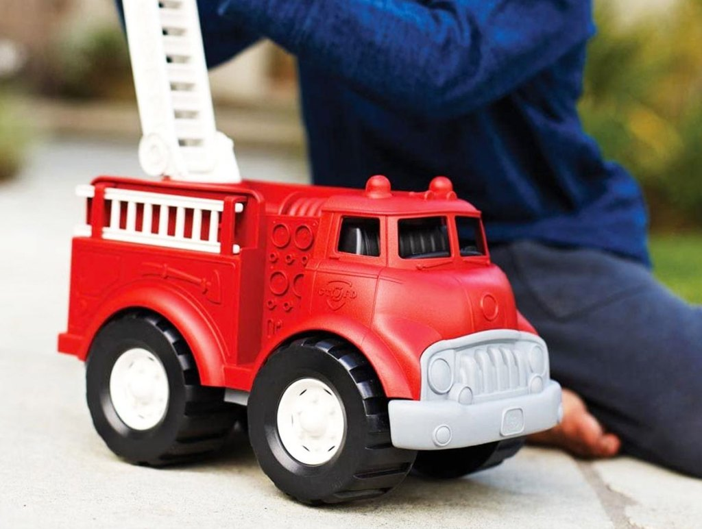 boy playing with a red firetruck toy with moveable ladder