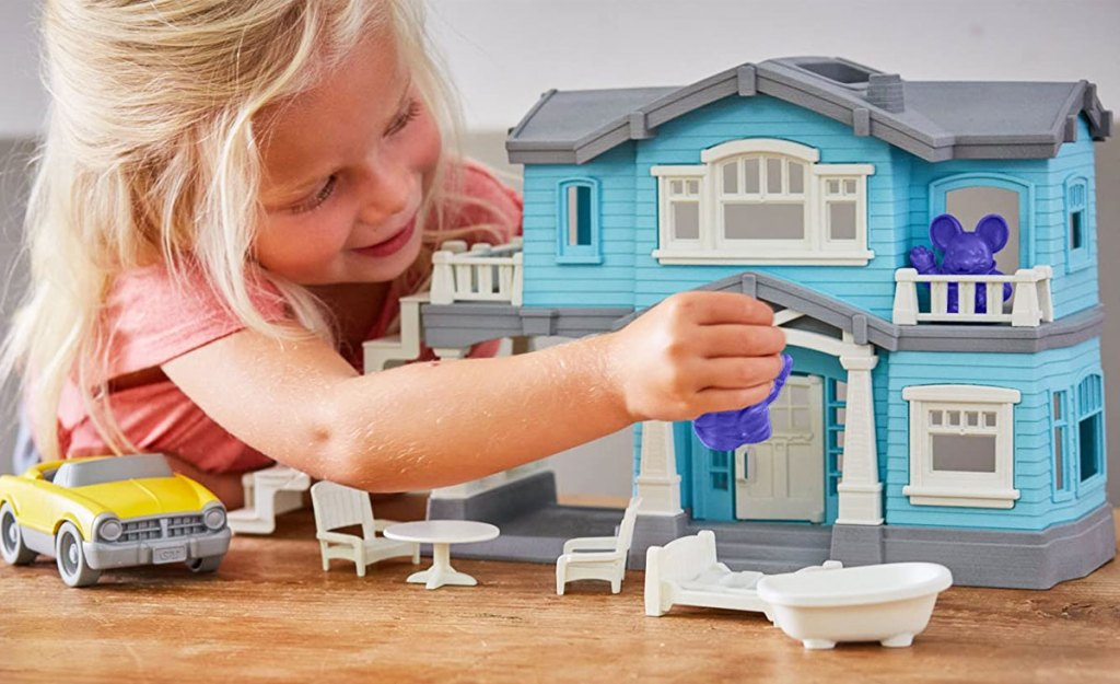 girl playing with a blue house playset