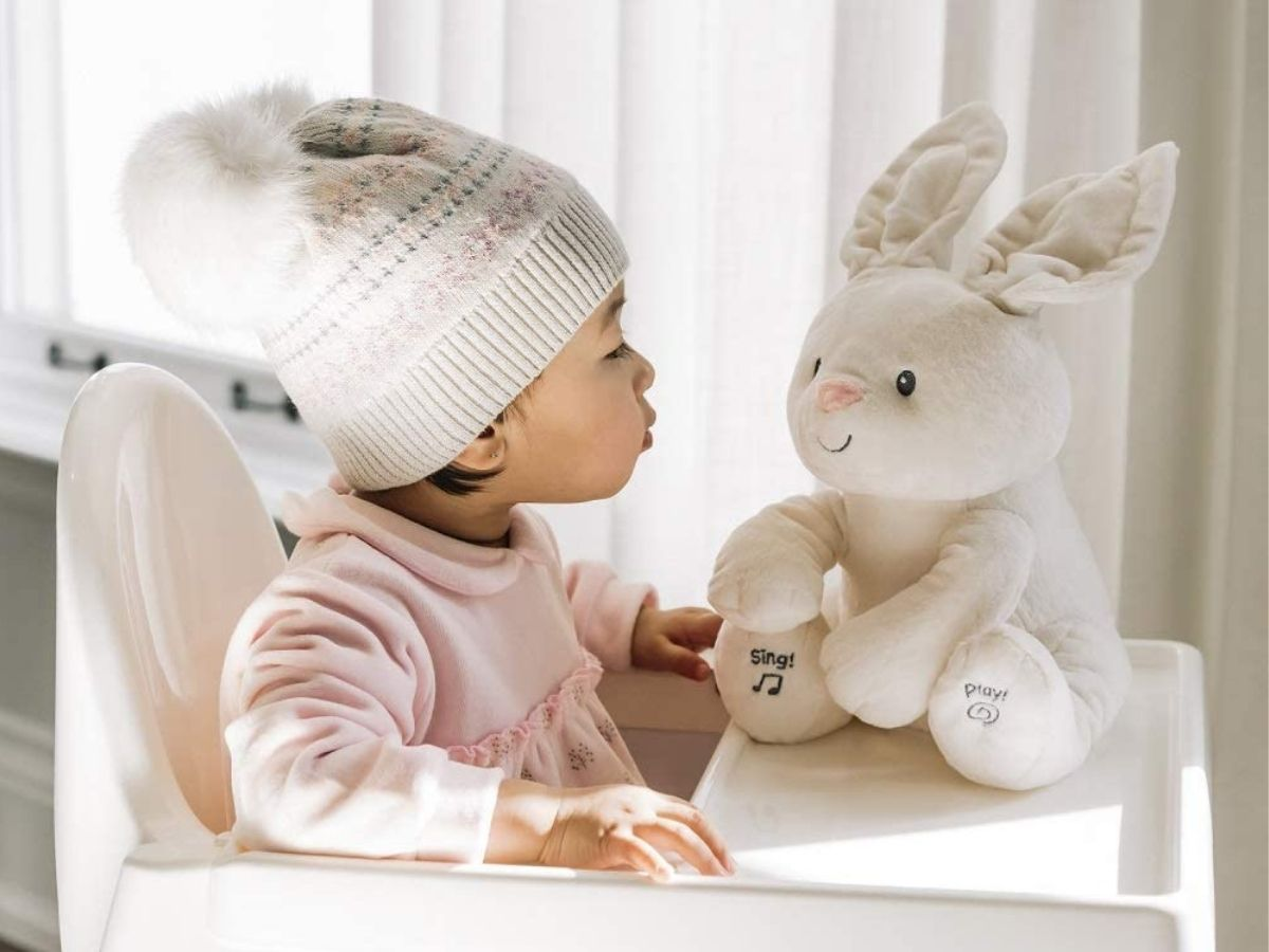 baby sitting in high chair with bunny on tray